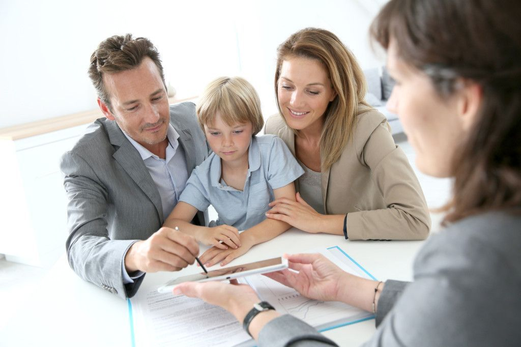 Family signing home purchase contract on tablet